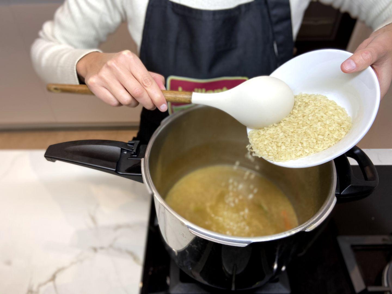 se añade el arroz a la olla junto con la carne
