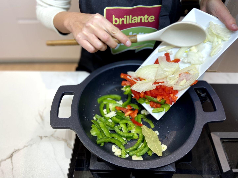 añadiendo la cebolla, el pimiento verde y el pimiento rojo a la sartén