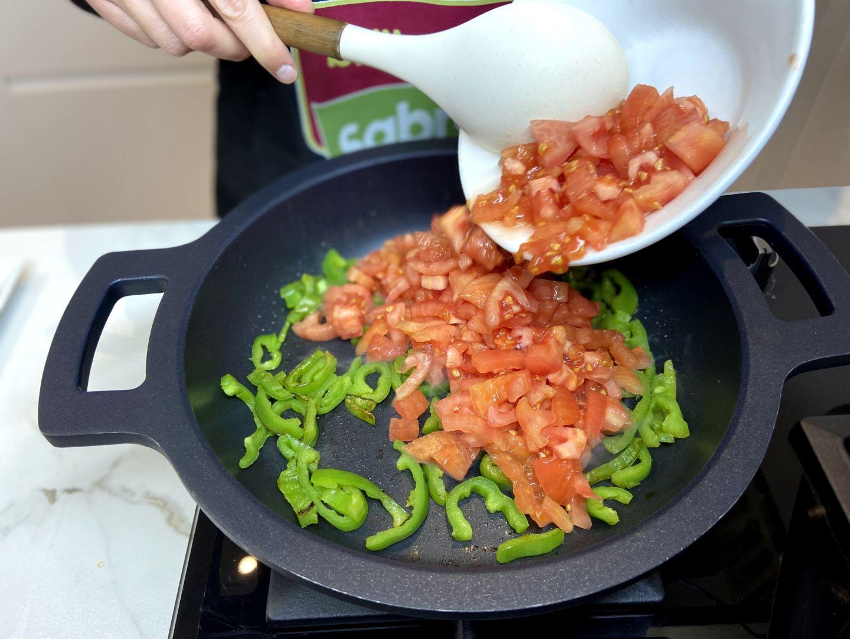 agregar los tomates troceados a los pimientos