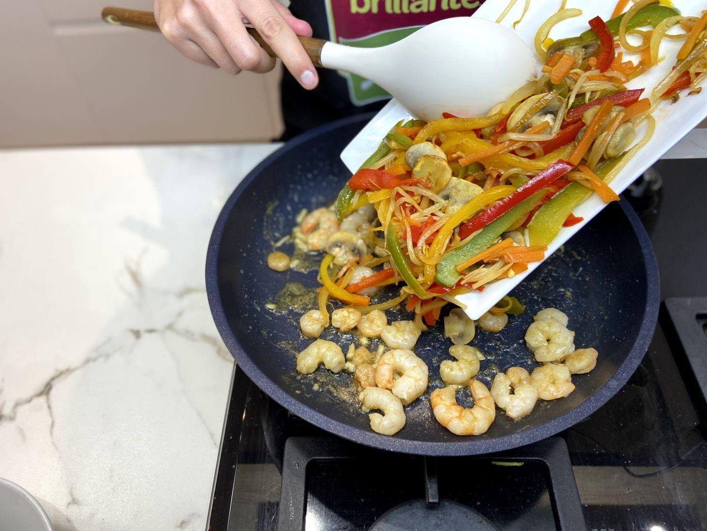 añadir las verduras salteadas a las gambas