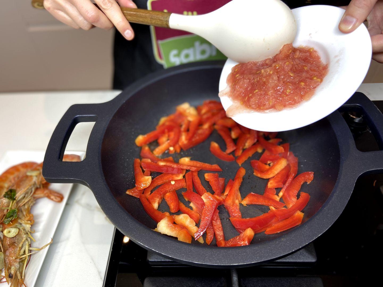 vertemos la mezcla de pimiento y tomate en la paellera caliente