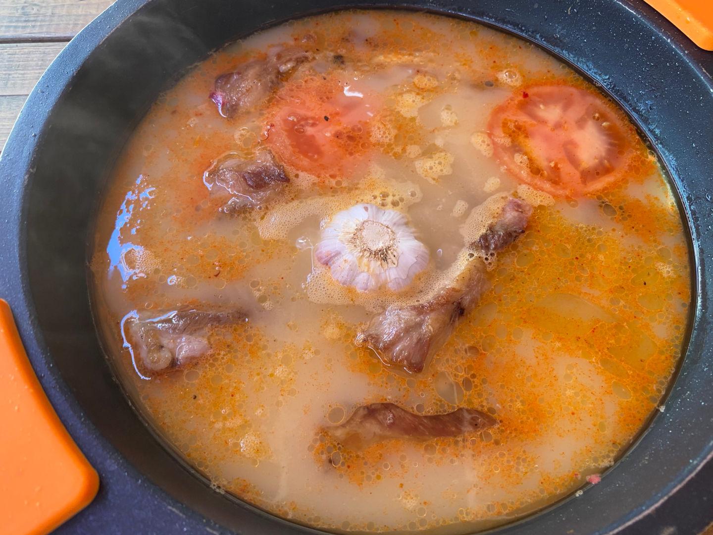 Añadimos los tomates, la cabeza de ajos, el caldo hirviendo y el azafrán